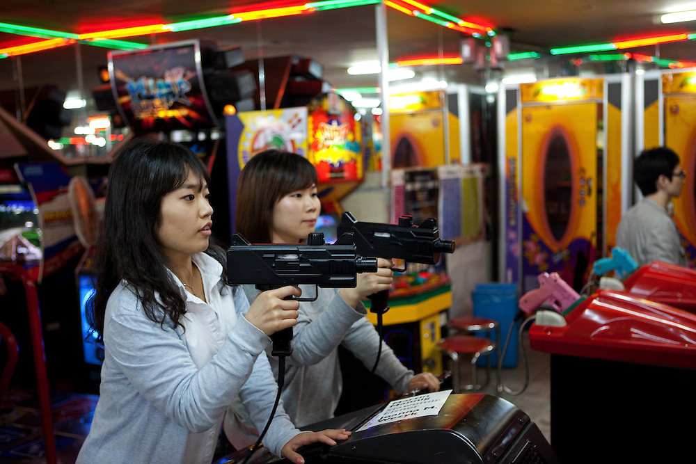 Seoul, South Korea, Republic of Korea, KOR, 24.04.2009: Two young girls are playing in the center of the Korean capital Seoul in an arcade a realistic shooter game.