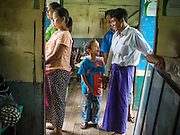 05 JUNE 2014 - YANGON, YANGON REGION, MYANMAR: A man and his son on the Yangon Circular Train. The Yangon Circular Train is a commuter train that circles Yangon, Myanmar (Rangoon, Burma). The train is 45 kilometers long, makes 38 stops and takes about three hours to make a loop of the city.     PHOTO BY JACK KURTZ