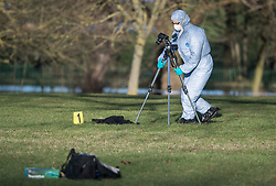 © Licensed to London News Pictures. 28/12/2017. London, UK. A police forensics officer photographs evidence near the scene in Finsbury Park where the body of a young woman was found on Boxing Day. A member of the public found the body of the woman, thought to be in her 20s, near the sports area in the centre of the park. Photo credit: Ben Cawthra/LNP