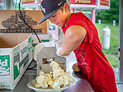 "26 JUNE 2020 - DES MOINES, IOWA: JAX (first name only) uses a drill to slice potatoes to make potato chips at Fair Food Friday in Des Moines. The 2020 Iowa State Fair, like many state fairs in the Midwest, has been cancelled this year because of the COVID-19 (Coronavirus) pandemic. The cancellation of the fair left many small vendors stranded with no income. Some of the fair food vendors in Iowa started ""Fair Food Fridays"" on a property a few miles south of the State Fairgrounds. People drive up and don't leave their cars while vendors bring them the usual midway fare; corndogs, fried tenderloin sandwiches, turkey legs, deep fried Oreos, lemonaide and smoothies. Fair Food Friday has been very successful. The vendors serve 450-500 people per Friday and during the lunch rush people wait in line in their cars 30 - 45 minutes to place an order.     PHOTO BY JACK KURTZ"