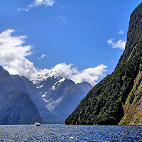 Introduction to Milford Sound at Fiordland, New Zealand<br /> The masterpiece of Fiordland National Park &ndash; New Zealand&rsquo;s largest park - is Milford Sound. Piopiotahi (Māori name) is the northernmost of the fjords along the southwestern coast of New Zealand. This incredible 9.9 mile inlet of the Tasman Sea is defined by sheer summits like Mount Kimberley (The Lion) at 4,271 feet on the left, the snow-capped Mills Peak at 5,987 feet and the 3,966 foot Cascade Peak on the right. Savor the pristine scenery above water during a sightseeing cruise. Marvel at the waterfalls. Enjoy seeing dolphins, penguins, fur seals and whales in the water. And stop at Harrison Cove (center) to view marine life at 32 feet underwater at the Milford Sound Underwater Observatory. You will soon understand why Milford Sound is rated among the world&rsquo;s top destinations.