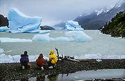 Woman and two girls watch icebergs on windy day, Lago Grey, Torres del Paine National Park, Patagonia, Chile.