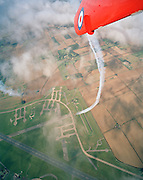 With the runways and former nuclear silos of RAF Scampton below, Lincolnshire, the elite 'Red Arrows', Britain's prestigious Royal Air Force aerobatic team swoop down to their home airfield during an In-Season Practice (ISP) training flight. Trailing white organic smoke before reforming in front of a local crowd they work through a 25-minute series of display manoeuvres that are loved by thousands at summer air shows. They curve round in a similar trajectory as seen on the bending taxi-way. Freshly-ploughed English fields with properties, roads, hedgerows and cold war nuclear solios are seen below on a perfect day for aerobatic displaying. After some time off, spare days like this are used to hone their manual aerobatic and piloting skills before re-joining the air show circuit. Since 1965 they've flown over 4,000 shows in 52 countries.   .