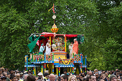© Licensed to London News Pictures. 09/06/2013. London, UK. Followers of the Hare Krishna movement are seen on a chariot in Hyde Park, London, today (09/06/2013) as it is pulled to Trafalgar Square as part of the 'Hare Krishna' festival of 'Rathayatra'. The parade, also known as the 'Festival of Chariots', is the biggest street festival celebrated by members of the Krishna followers and, in London, features three huge, wooden chariots containing the smiling figures of Lord Jagannatha, Lady Subhadra and Lord Balarama being pulled by hand from Hyde Park to Trafalgar Square.  Photo credit: Matt Cetti-Roberts/LNP