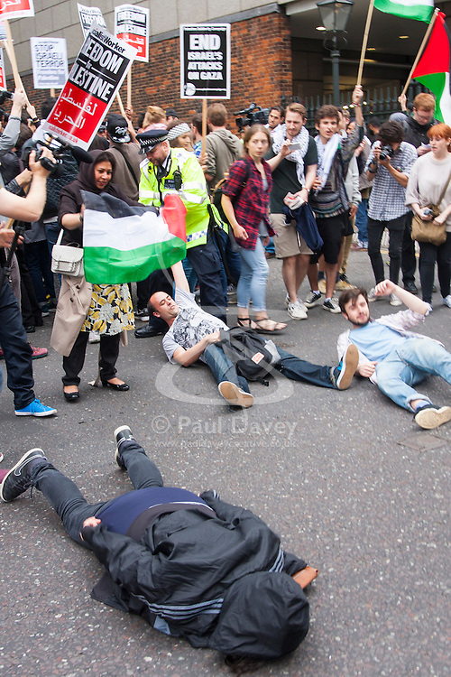 """London, July 5th 2014. A police officer drags a """"die-in"""" protester off Kensington High Street as hundreds demonstrate near the Israeli embassy in London against the ongoing occupation of Palestine and the west's support of """"Israel's collective punishment of Palestinians""""."""