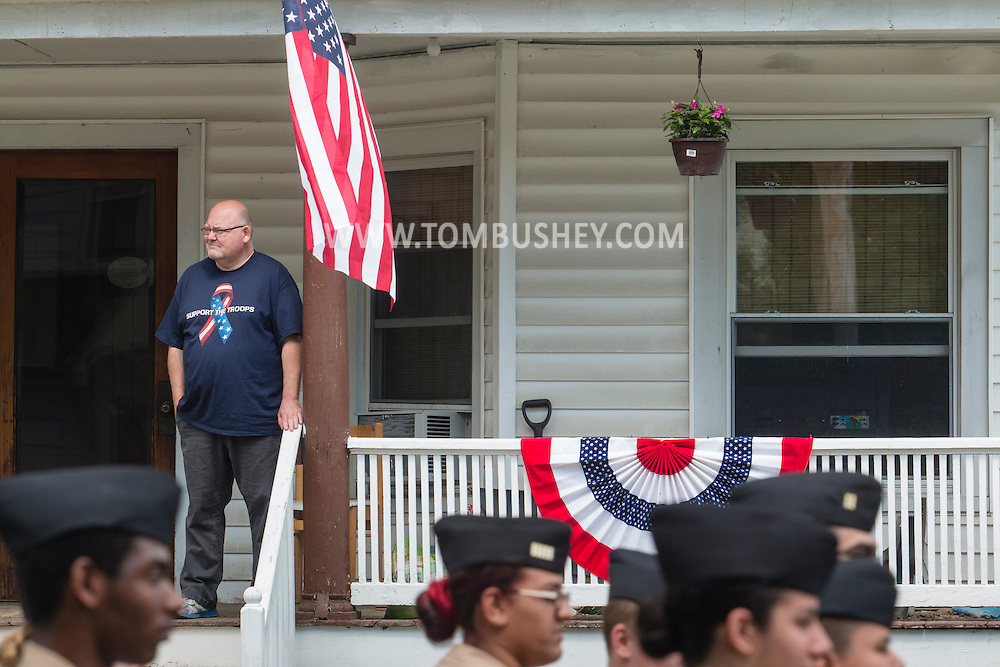 Middletown, New York - A man watches from his porch as marchers in the Middletown-Town of Wallkill Memorial Day parade head down Highland Avenue on May 25, 2015.