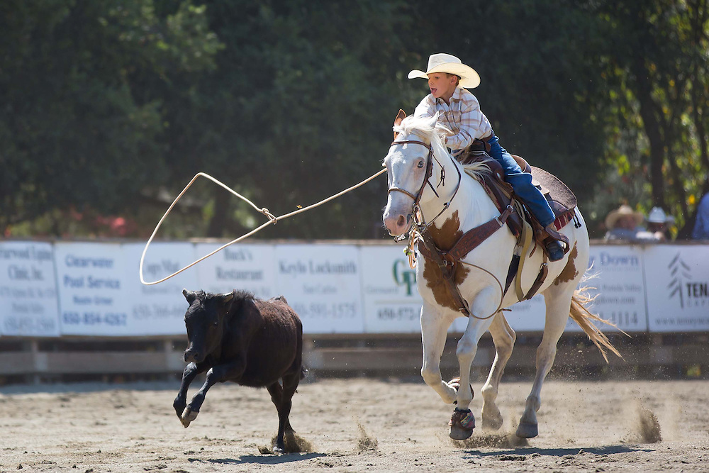 A participant in the breakaway roping category swings his rope towards his moving target during the 63rd Annual Woodside Junior Rodeo