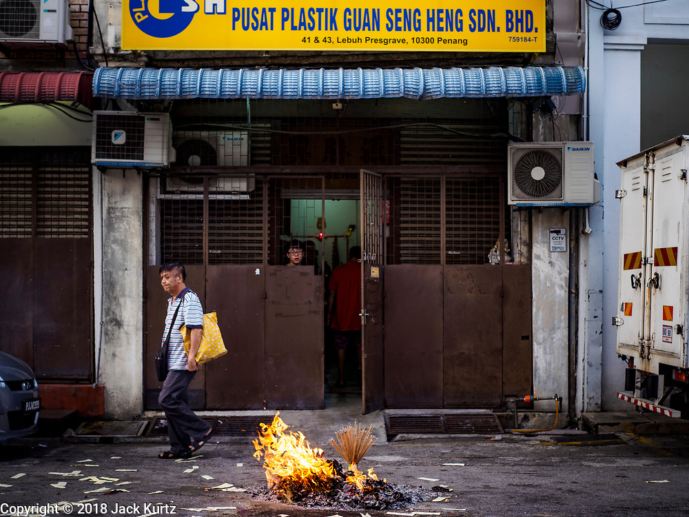 24 AUGUST 2018 - GEORGE TOWN, PENANG, MALAYSIA: A pedestrian walks past a pile of ghost money during Hungry Ghost Month in George Town. The Ghost Festival, also known as the Hungry Ghost Festival is a traditional Buddhist and Taoist festival held in Chinese communities throughout Asia. The Ghost Festival, also called Ghost Day, is on the 15th night of the seventh month (25 August in 2018). During Ghost Festival, the deceased are believed to visit the living. In many Chinese communities, there are Chinese operas and puppet shows and elaborate banquets are staged to appease the ghosts.      PHOTO BY JACK KURTZ