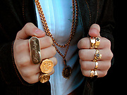 Close-up of teenage girl wearing gold sovereign rings and gold chains, London, 2000