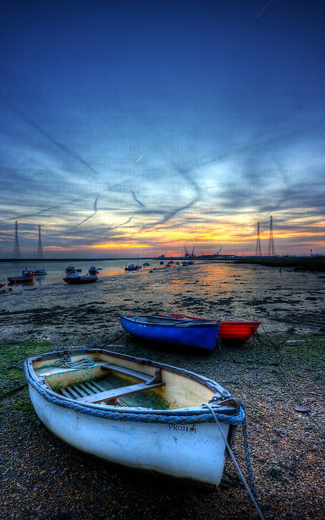 Early morning frosty mid winter sunrise over the river swale and low tide mud flats and boats and with ridham dock in the distance