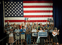 """First Lady Michelle Obama gets the audience fired up during her """"It Takes One"""" speech at Laconia Middle School Thursday afternoon.  (Karen Bobotas/for the Laconia Daily Sun)"""