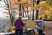 "Painters capture gorgeous fall clors. In Letchworth State Park, renowned as the ""Grand Canyon of the East,"" the Genesee River roars northeast through a gorge over three major waterfalls between cliffs as high as 550 feet, surrounded by diverse forests which turn bright fall colors in the last three weeks of October. The large park stretches 17 miles between Portageville and Mount Morris in the state of New York, USA. Drive or hike to many scenic viewpoints along the west side of the gorge. The best walk is along Gorge Trail #1 above Portage Canyon from Lower Genesee Falls (70 ft high), to Inspiration Point, to Middle Genesee Falls (tallest, 107 ft), to Upper Genesee Falls (70 ft high). High above Upper Falls is the railroad trestle of Portageville Bridge, built in 1875, to be replaced 2015-2016. Geologic history: in the Devonian Period (360 to 420 million years ago), sediments from the ancestral Appalachian mountains eroded into an ancient inland sea and became the bedrock (mostly shales with some layers of limestone and sandstone plus marine fossils) now exposed in the gorge. Genesee River Gorge is very young, as it was cut after the last continental glacier diverted the river only 10,000 years ago. The native Seneca people were largely forced out after the American Revolutionary War, as they had been allies of the defeated British. Letchworth's huge campground has 270 generously-spaced electric sites."