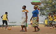 Women carry on with their daily chores carrying goods as they pass children playing football..Kumasi, Ghana, West Africa, Africa.© Demelza Cloke