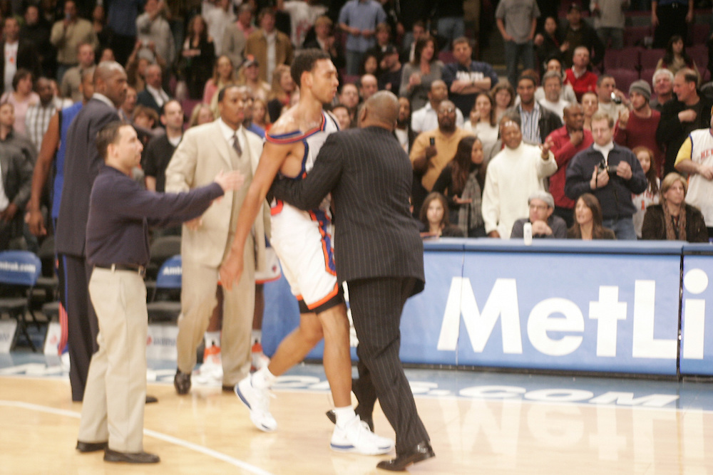 Jared Jeffies of the New York Knicks is restrained during a fight against the Denver Nuggets at Madison Square Garden, New York on Saturday  16 December 2006. (Andrew Gombert for The New York Times)