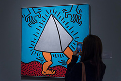 "© Licensed to London News Pictures. 01/10/2018. LONDON, UK. A visitor photographs ""Untitled"", 1985, by Keith Haring (Est. GBP700,000 - 900,000). Preview of artworks in Sotheby's Frieze sales at Sotheby's New Bond Street.  The auction will take place 5 October during Frieze and Frieze Masters – the world's most vibrant Contemporary and Modern art fairs.  Photo credit: Stephen Chung/LNP"