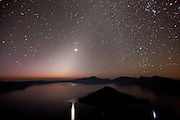 A natural nighttime pillar of light known as the Zodiacal Light shines above and is reflected in Crater Lake, Oregon. The Zodiacal Light results from the sun shining on dust particles from old comets. The dust particles - the largest of which are believed to be just 0.3 mm and miles from its nearest neighboring particle - orbit the sun in a range from Mars to beyond Jupiter. Visible year-round in the tropics, the Zodiacal Light is best viewed immediately around the spring and fall solstice farther from the equator. The planet Venus, the brightest object in the sky, is visible near the peak of the Zodiacal Light and is also reflected in Crater Lake. The Milky Way, visible on the right, intersects with the Zodiacal Light at the top-center of the image. Crater Lake, which is actually a caldera, formed when Mount Mazama erupted violently about 7,700 years ago, causing its summit to collapse. Subsequent eruptions sealed the caldera, trapping rain water and snowmelt, forming the lake, which has a maximum depth of 1,949 feet (594 meters). Wizard Island, a volcanic cinder code, is visible in the foreground.