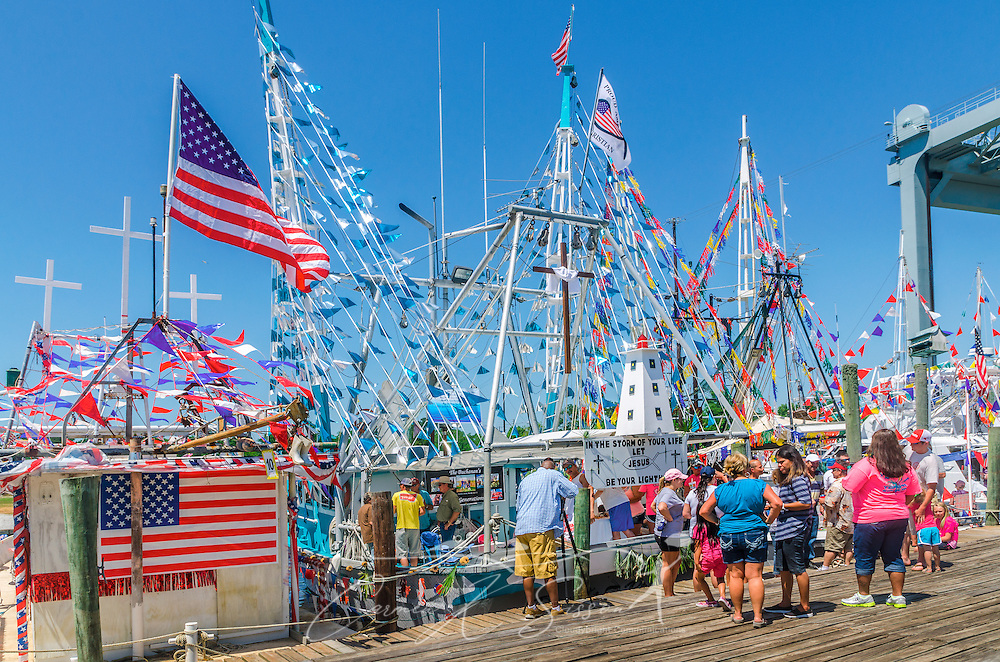 """Decorated boats, including """"Why Bother"""" and """"David's Pride,"""" line up along the dock during the 65th annual Blessing of the Fleet in Bayou La Batre, Alabama, May 4, 2014. The first fleet blessing was held by St. Margaret's Catholic Church in 1949, carrying on a long European tradition of asking God's favor for a bountiful seafood harvest and protection from the perils of the sea. The highlight of the event is a blessing of the boats by the local Catholic archbishop and the tossing of a ceremonial wreath in memory of those who have lost their lives at sea. The event also includes a land parade and a parade of decorated boats that slowly cruise through the bayou. (Photo by Carmen K. Sisson/Cloudybright)"""