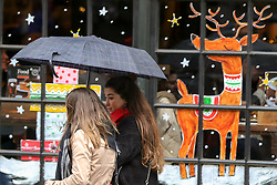 © Licensed to London News Pictures. 8/112/2018. London, UK. Tourists with an umbrella in front of a window of a pub decorated with Christmas artwork during rain and wet weather in Westminster. Photo credit: Dinendra Haria/LNP
