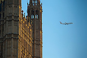 A plane flying past the Palace of Westminster, also known as the Houses of Parliament or Westminster Palace.  It is the meeting place of the two houses of the Parliament of the United Kingdom and is on the bank of the river Thames in London.