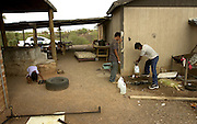 Undocumented migrants, who crossed from Mexico illegally in to the United States on to the Tohono O'odham Nation in Arizona, refill water bottles at a residence before continuing to cross the Sonoran Desert, USA.
