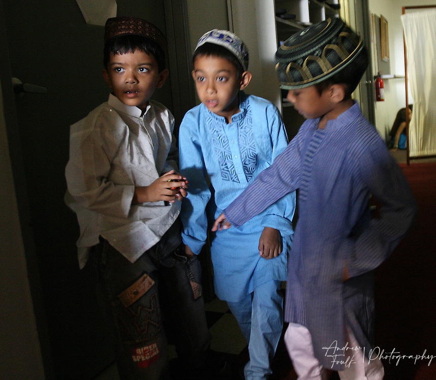 /Andrew Foulk/For The Californian/.Sajid Khan,8, (center) looks up as he and his brother Raiyan, 6, (right) and friend Xyrus, are told to take a seat and stop playing as prayer starts during the last day of Ramadan, at the  Islamic Center of Temecula.