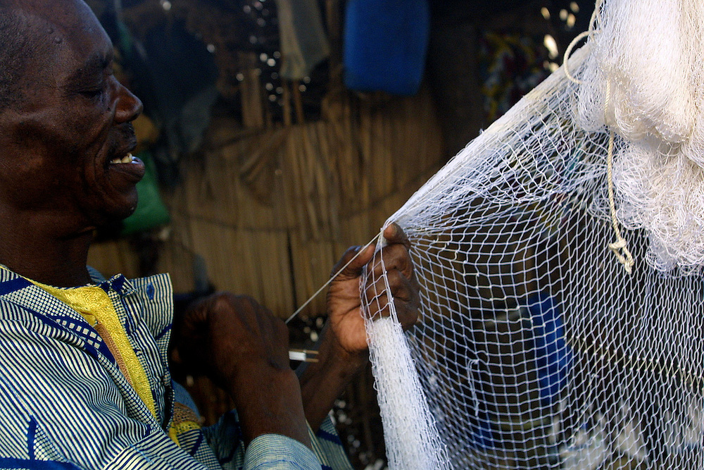 Benin November 27, 2001 - Beninese fisherman in northem of Cotonou threads an hold fishing net