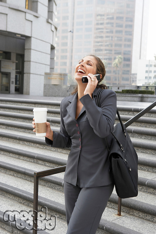 Business woman laughing on mobile phone in city