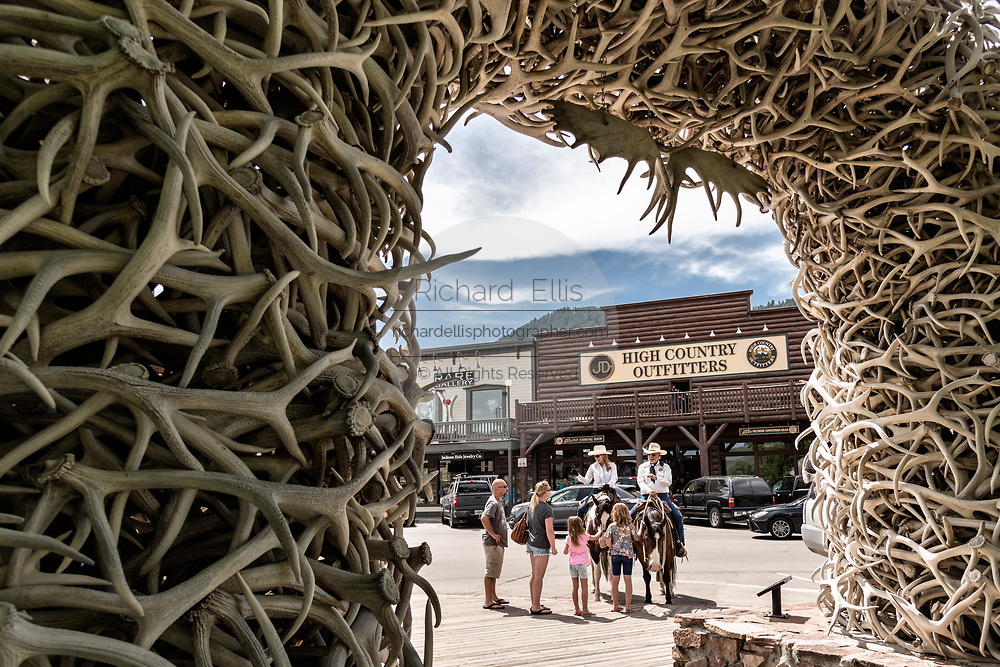 Jackson Police Mounted Patrol officers stop to chat with tourists seen through the Elk Antler Arch in George Washington Memorial Park, known as the Town Square in Jackson Hole, Wyoming. The Town Square's four arches are built entirely from local elk antlers. Each arch is supported by a steel framework and constructed by hand using more than 2,000 antlers each. The arches are held together mostly by friction and gravity and need to be rebuilt about every 50 years.