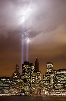 The lights of the downtown New York City skyline reflect off the East River on a cloudy night.  The lights from the World Trade Center Memorial create an eerie glow in the clouds.