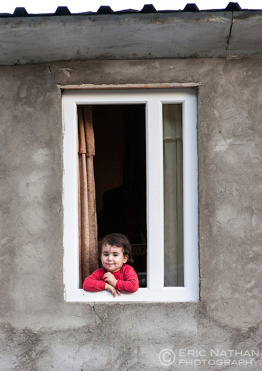 A young girl at the window of a house in Zhibiani, one of four hamlets comprising Ushguli community in Svaneti district, Caucasus Mountains, northern Georgia. Ushguli is considered the highest permanently inhabited village in Europe (2200m).