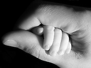 Mother holding her baby's hand