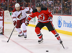 Mar 27, 2014; Newark, NJ, USA; New Jersey Devils right wing Damien Brunner (12) protects the puck from Phoenix Coyotes center Martin Hanzal (11) during the first period at Prudential Center.