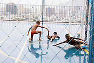 Boys playing football in the rain, at a youth centre in Cantagalo, Zone Sul, Rio de Janeiro, Brazil, October 2006