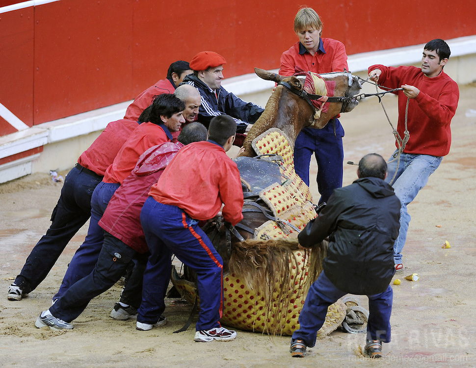 "Some ""monosabios"" help a picador horse to stand up as it falled down because of the soaked sand of the bull-ring, during the sixth corrida of the San Fermin festivities, on July 12, 2008, in Pamplona, north of Spain."