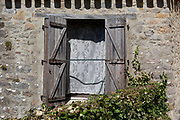 Open wooden shutters and traditional lace curtains in the window of a house, on 24th May, 2017, in Ribaute, Languedoc-Rousillon, south of France