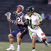 A member of the Boston Cannons keeps the ball away from a member of the New York Lizards during the game at Harvard Stadium on July 19, 2014 in Boston, Massachusetts. (Photo by Elan Kawesch)