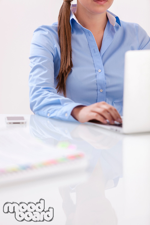 Close-up view of beautiful woman using laptop at desk