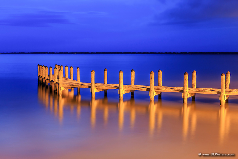 Golden pier at twilight, jutting out into Currituck Sound on the Outer Banks, NC. The warm parking lot lights shining onto the pier contrast  with the deep blue twilight.