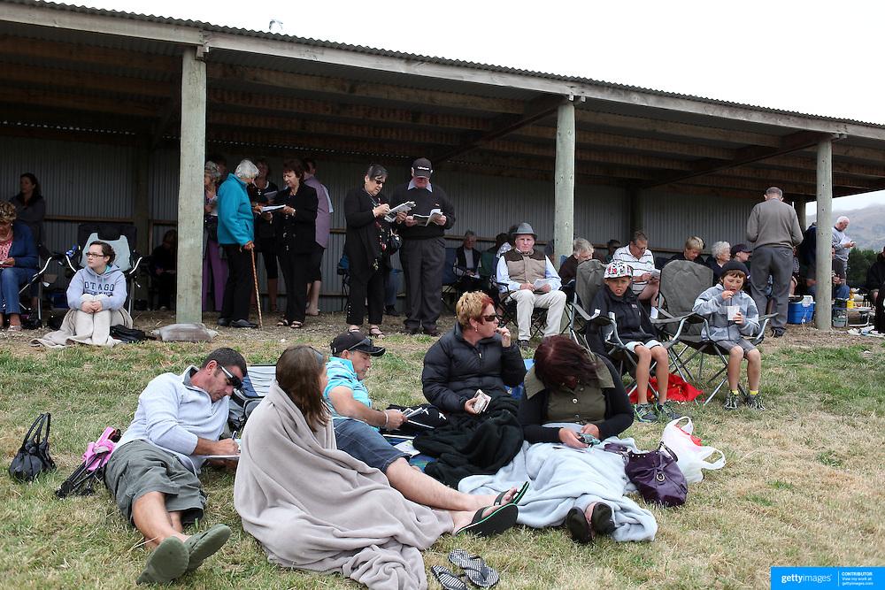 Spectators study form during the Roxburgh Trotting Club Summer Festival Races, Roxburgh, Otago, New Zealand. 5th January 2012