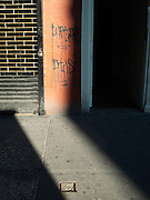 A shaft of light illuminating the sidewalk and front gate of an old building with graffiti in the Greenwich Village neighborhood of Manhattan, New York City.