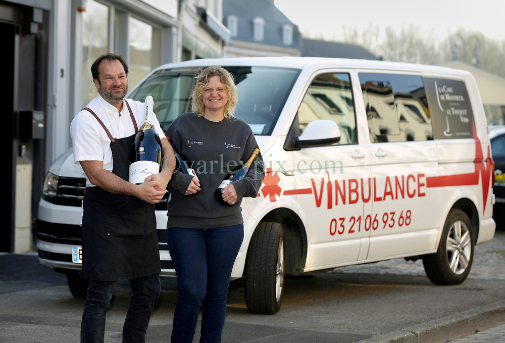 09 April 2020. Montreuil Sur Mer, Pas de Calais, France.<br /> The 'Vinbulance.' The 4th emergency service delivering wine, beer and spirits in and around Le Touquet and Montreuil Sur Mer in Hauts de France, 1 hour south of Calais.<br /> Olivier and Belinda Tirel, (both 45 yrs old) owners of La Cave de Montreuil and Le Touquet with their emergency vehicle, the 'Vinbulance.' <br /> <br /> Belinda, an Australian met Olivier, a Frenchman in England when they both worked at Café Rouge in Kew Gardens in London in 1996. Married 24 years with 4  children they own 2 wine shops, one in Le Touquet (since 2007) and one in Montreuil Sur Mer (since 2015). <br /> <br /> Belinda came up with the idea of the 'Vinbulance' having seen a photo of a 'winebulance' on the internet. Olivier and Belinda contacted friends who are doctors, nurses and medical technicians before embarking on the idea. They wanted to check that their idea would not be offensive to those working on the front lines against coronavirus. All their friends in the medical profession thought it would be an excellent idea to try and cheer people up, bring a smile to their faces and help lift people's spirits in these difficult times. 'Which was the point of it,' explained Olivier.<br /> <br /> 'People give us thumbs up, toot their horns and wave when they see the 'vinbulance.' Belinda was stopped twice in the past 2 days with people asking to take photos of her and the 'vinbulance' explained Olivier. 'One person, a regular customer even ordered some wine because he did not know we were open.'<br /> <br /> 'The coronavirus crisis has badly affected business. We have lost all of our restaurant trade and people just are not having parties and celebrating as they were before all this,' explained Olivier.<br /> <br /> 'We are considered a business of 'première nécessité,' (first necessity) as declared by the  French Government which means we can remain open. We don't get any help from the government financially, we have 4 children and a Brazilian exchange student who is staying with us beca