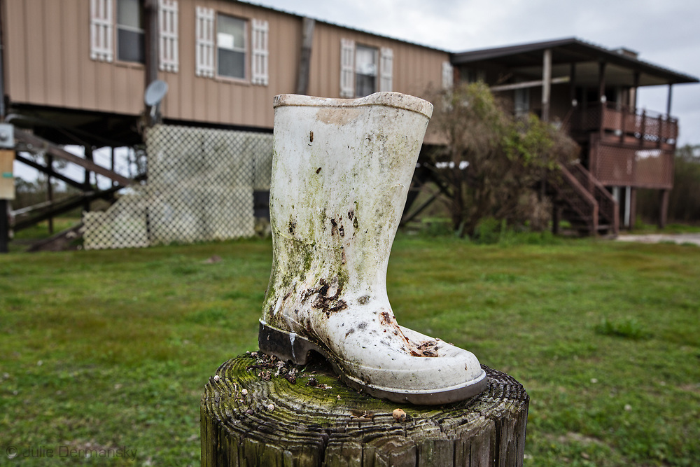 Boot on a  post in front of an abandoned home on Isle de Jean Charles, in Louisiana.