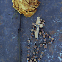 Squashed dried rose once cream and now brown lying with its stem on rusty metal sheet next to rosary with crucifix