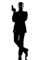 one caucasian secret agent in a james bond posture holding gun full length silhouette in studio isolated white background