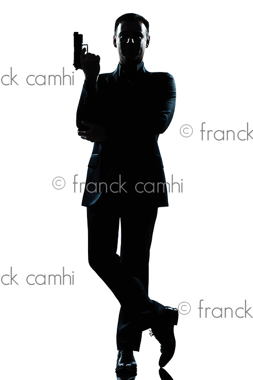 one caucasian secret agent in a james bond posture holding gun full length silhouette in studio isolated white background
