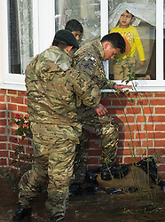 © London News Pictures. 12/02/2014. Egham, UK.  A boy looks out of his window as members of a Gurkha regiment lay sandbags in Egham in Surrey. Torrential rain in the area is due to raise water levels increasing the risk of further flooding. Photo credit : Ben Cawthra/LNP