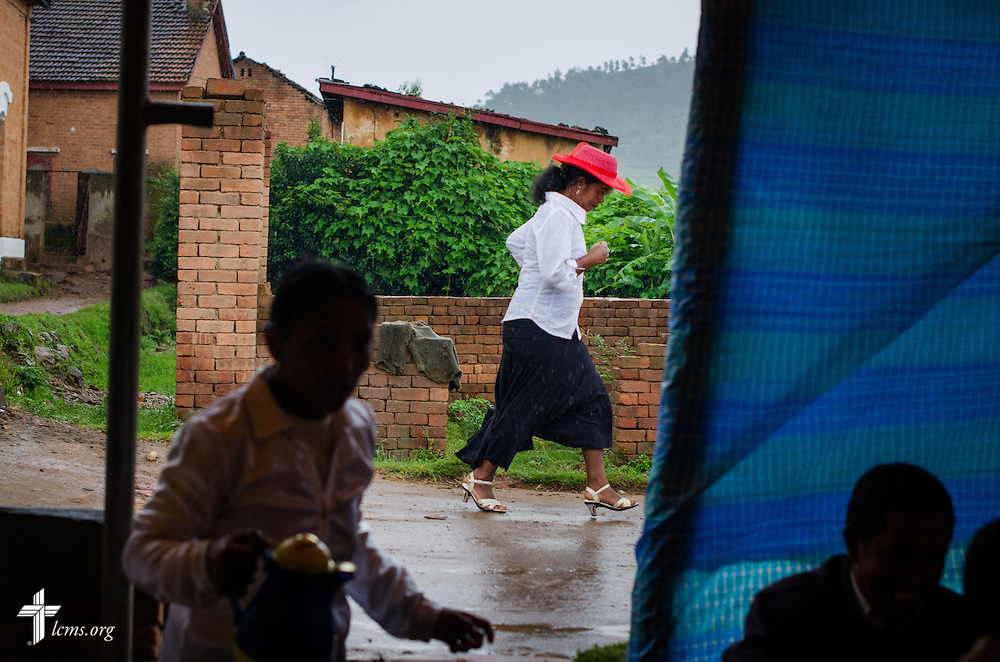 A woman runs for shelter during a downpour after the opening of the synodical convention for the Fiangonana Loterana Malagasy at a Lutheran church near Antsirabe, Madagascar, on Wednesday, Feb. 5, 2014. LCMS Communications/Erik M. Lunsford