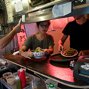 Servers pick up finished dishes from the kitchen during the lunch rush as Chef Danny Bowien's restaurant, Mission Chinese, at its New York City location on the Lower East Side of Manhattan on Tuesday, July 31, 2012 in New York, NY..