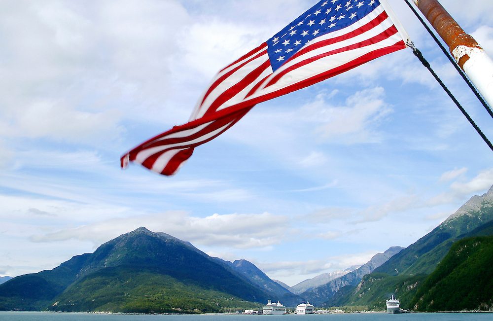 USA, Alaska,Taiya Inlet, Skagway, Coast Mountains, The U.S.A. flag waves over a view of Skagway Harbour and cruise liners from the back of an Alaska Ferry.