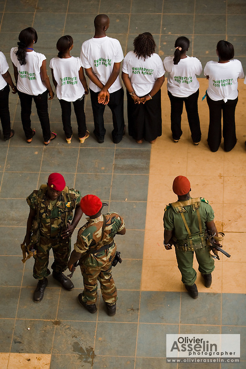 "Soldiers stand guard by a group of students during the visit of Guinea's president Captain Moussa Dadis Camara at the Kofi Annan private university in Conakry, Guinea on Thursday March 5, 2009. Camara, who took power after a coup in December 2008, was visiting the university to ""meet the youth"", as part of his efforts to solidify his support from Guinea's population.(Olivier Asselin for the New York Times)"